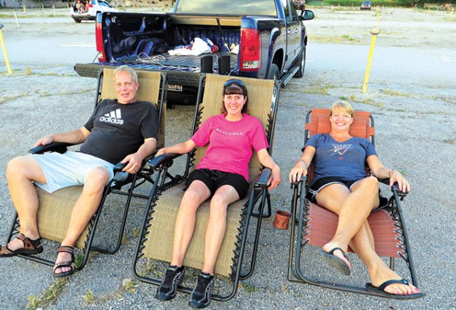 Lloyd and Charlotte Kutch (left and middle) and Brenda Bischoff join other early arrivers as they prepare for the first of two first-run movies. Lloyd wired in jacks to the back of his truck to plug in speakers especially for their visits to the Winchester. (Brett Dickerson)