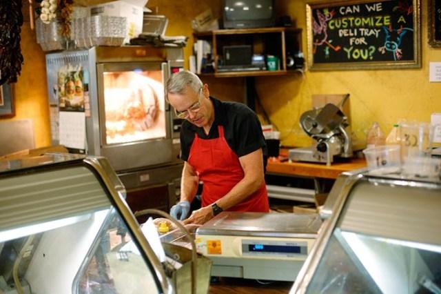 Bill Kamp prepares rib-eye steaks at Bill Kamp's Meat Market. (Garett Fisbeck)