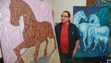"Artist and teacher, Carlos Tello with work in his living room including, ""Aztec Horse, left, and ""Blue Moon"", both will be featured during this years Fiestas de las Americas on October 3rd, 9-17-15.  (Mark Hancock)"