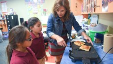 4th graders, from left, Renee Alvarado and Destiny Longoria, get a little instruction during an after school cooking class from Principal and After School Ambassidor for the State of Oklahoma, Kim Templeman, at Crooked Oak Public Shools, 11-3-15.  (Mark Hancock)