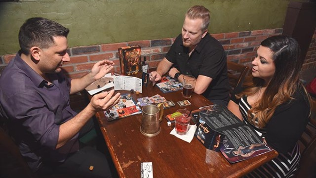 From left, Anthony Vandyousefi, with Johnnie and Layla Payne, get into a (Moch) game of Firefly over drinks, 10-7-15.  (Mark Hancock)