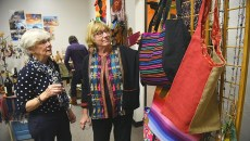From left, Patty Tepper-Rasmussen and Linda Temple look over fair trade products for sale during a grand opening of the PAMPE Ghana's Global Market, 6516 N. Olie, Friday, 11-13-15.  (Mark Hancock)