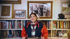 Tracey Satepauhoodle-Mikkanen, executive director of Jacobson House Native Art Center, in the center's cramped office with a historic portrait of the Kiowa Five and Oscar Brousse Jacobson over her shoulder.  The original Kiowa Five included a woman, Lowis Somoky, who steped out and was replaced by James Auchieh.  Officials now refer to the group as the Kiowa Six, puting Smoky back into the group.  2-8-16, at the Jacobson House, 609 Chautauqua Avenue, Norman Oklahoma.  (Mark Hancock)