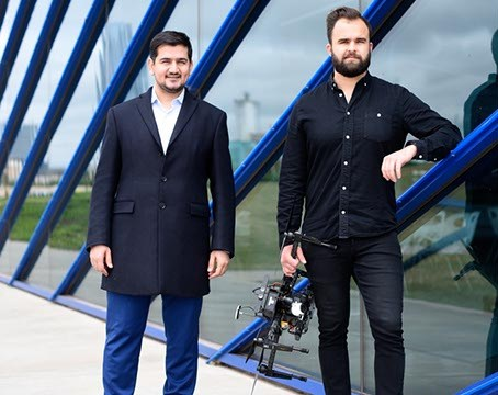 Ersin Demirci and Nick Brown pose for a photo with drones at the Boathouse District, Monday, April 11, 2016.  (Garett Fisbeck)