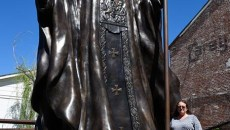 Teresa Clark poses for a photo with a 20-foot-tall monument to Pope John Paul II that she designed, at The Crucible Foundry in Norman, Thursday, May 12, 2016.  (Garett Fisbeck)