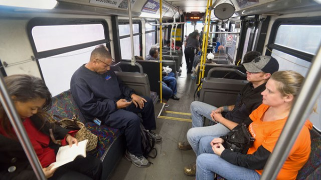 Passengers get comfortable near the rear of the Route 5 bus as it continues to board at the Embark downtown transite station, 3:30 pm, 11-20-15.  (Mark Hancock)