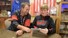Rob Davis works with Erik Sproul in his classroom at Yukon High School. | Photo Garett Fisbeck