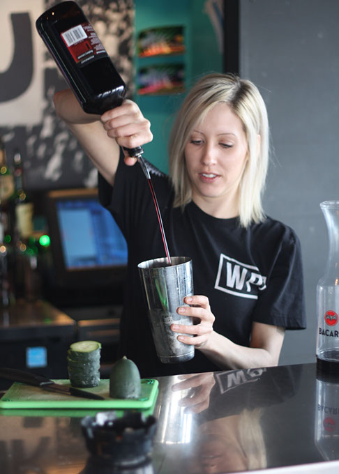Bartender Katie Wicks pours coconut rum in a Sweet Pete at Guyutes. (Greg Elwell)