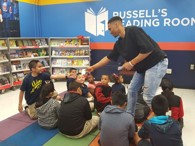 Russell Westbrook handed out gift certificates at the opening of his Russell's Reading Room at Adams Elementary on March 21. (Michael Kinney / for <em>Gazette</em>)