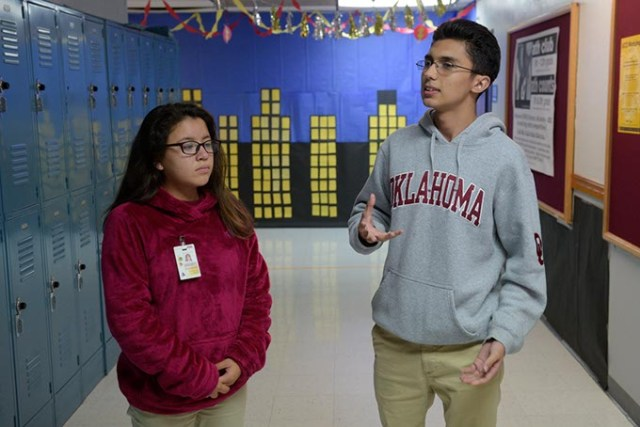 Senior Omar Camacho <em>right</em> explains how local college students visit Dove Science Academy OKC on Thursdays to mentor and help students like himself and Damaris Palma left with science homework. (Garett Fisbeck)