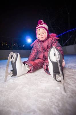 girl in skates sit on ice rink after fall