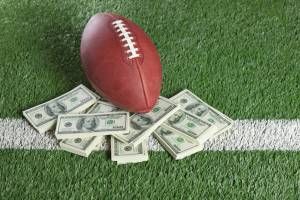 NFL football on field with a pile of money