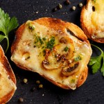 Crostini with melted cheese, mushrooms and fresh parsley