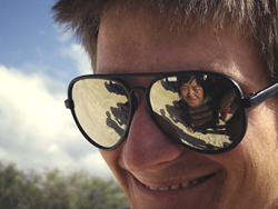 Man smiling with the reflection of a small girl in his glasses
