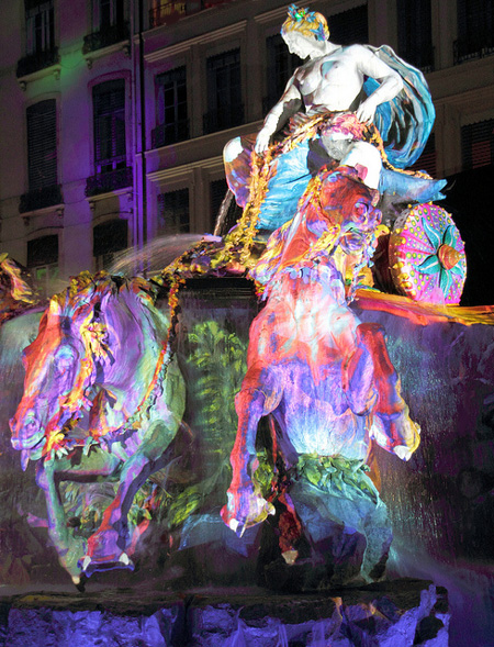 A statue during the Lyon Festival of Lights covered in coloured lights