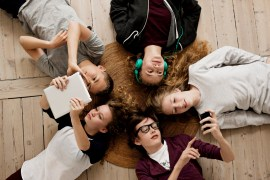 Teenagers lying on floor with Ipad and mobile