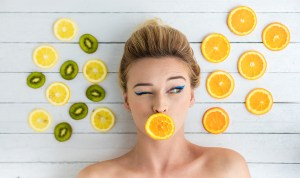beautiful blonde woman laying on a white wooden background next to slices of orange lemon and kiwi. With orange on mouth