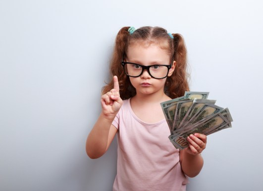 Cute kid girl holding dollars and have an idea how earning much money in crisis. Serious child teaching in eyeglasses