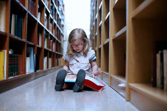 Girl Reading Book in Library --- Image by © Tim Pannell/Corbis