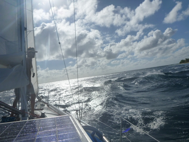 sailing through waves in tuamotus on the horizon line bri and rob travel and sailing adventure