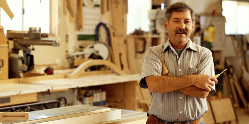 OWNER OF WOODWORKING SHOP WITH ARMS FOLDED, PORTRAIT