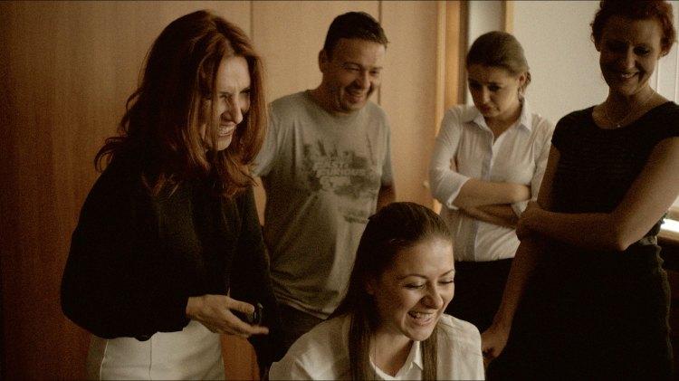 Julia og staben hennes ler av Tsankos stamming på bakrommet. (Foto: Tour de Force)