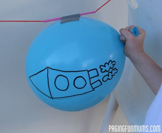 Holding the balloon opening tightly with your fingers so the air doesn ...
