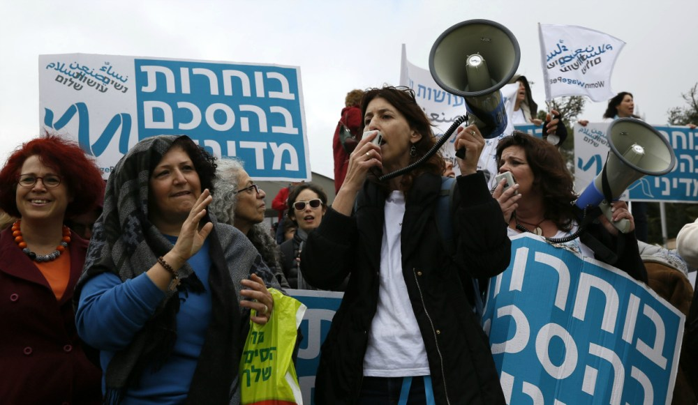 "Israeli women shout slogans during a march outside the Knesset (Israeli Parliament) in Jerusalem on March 4, 2015 as part of an initiative called ""Women wage Peace"" urging lawmakers to act for a political agreement with the Palestinians. The placards read in Hebrew ""Choosing a political agreement"".  AFP PHOTO / GALI TIBBON        (Photo credit should read GALI TIBBON/AFP/Getty Images)"