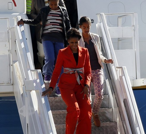 U.S. first lady Michelle Obama is followed by her daughters and her mother after arriving at the Sir Seretse Khama International Airport in Gaborone
