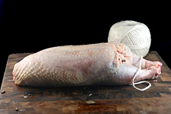 Tying whole deboned, red rice stuffed chicken for Chicken Ballotine