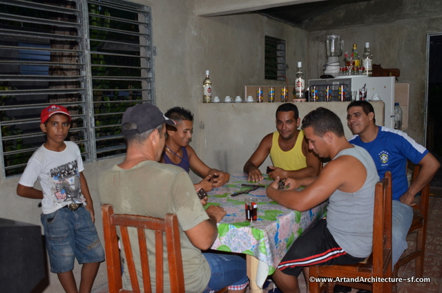The men play cards while the women prepare dinner