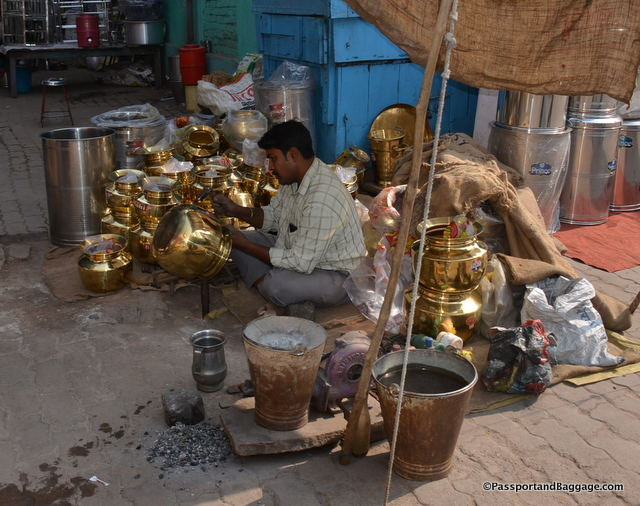 A fellow repairing his wares before selling them.
