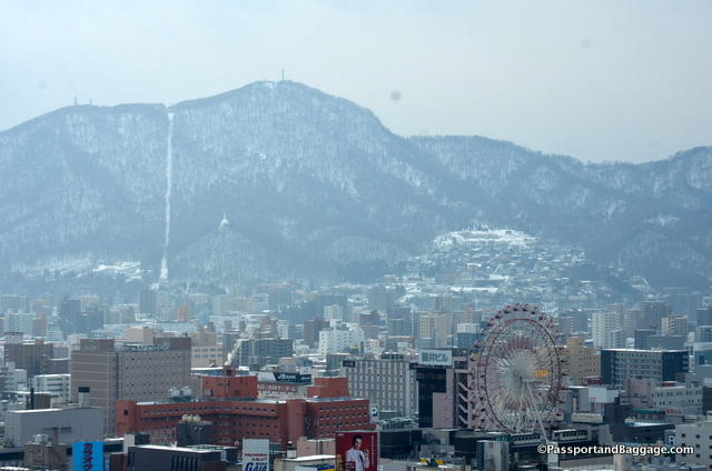 the Noria Ferris wheel at the Norbesa Center in the Susukino Entertainment district, and ski resorts in the distance from the observation tower