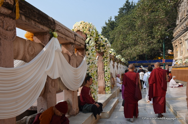 There is a wall around the Bhodi tree that serves as a walkway for pilgrims to chant and walk, they decorated with cloth, and then came in and placed silk flowers completely around the two archways that allow access to other areas of the grounds