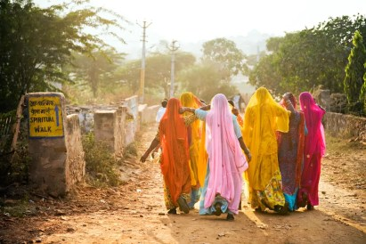 Women in colorful saris walking to Temple. India.