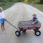 Stella Schafer pulls her younger brother Sam in a red wagon, along a sandy path.