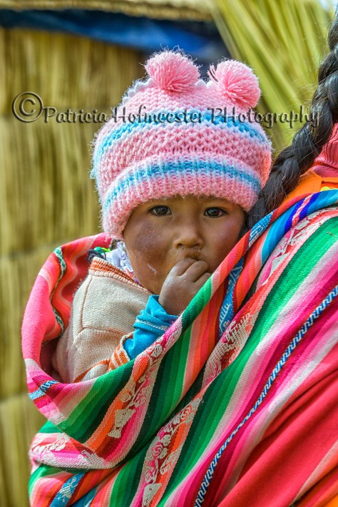 Baby carried by mother at Islas Flotantes, Reed Islands, Lake Titicaca, Peru
