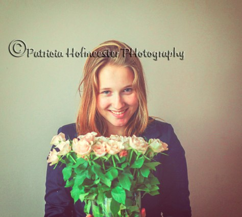 Pretty young woman holding a bouquet of pink roses