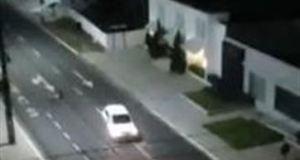 Imagens – feitas de um apartamento - mostram quando o travesti caminha pela calçada e passa um carro em alta velocidade, na contramão