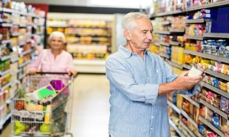 Senior man looking at canned food