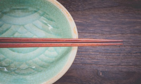 chopsticks and celadon green ceramic on wood table background