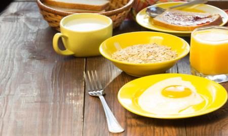 Breakfast served in yellow tableware - eggs, oatmeal, orange jui