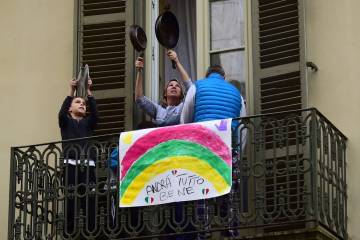 x87494574_people-look-out-of-their-apartment-windows-as-part-of-a-flashmob-organised-to-raise-morale-jpg-pagespeed-ic-amipfxdxxm