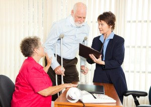 Injured man and his wife meet with a personal injury lawyer.