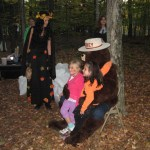 Kathy Whalen as the Autumn Queen and Scotty Weborg as Smokey Bear hand out treat bags at the end of the trail.