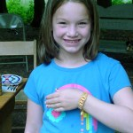 Peninsula State Park Camper Haily, age seven, shows off a wampum bracelet she beaded at Peninsula's Nature Center.