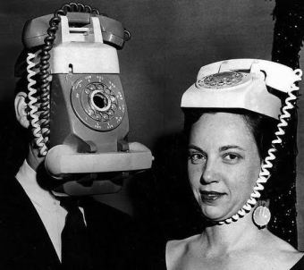 Black and white photograph of man and woman with old style phones attached to their heads.