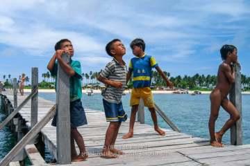 Sur le ponton de Mabul, les petits gitans de la mer accueillent les plongeurs. Bornéo, Malaisie. Juillet 2006.