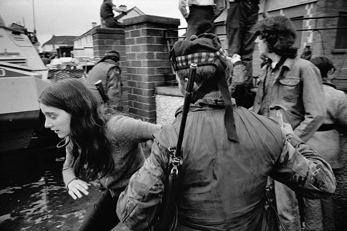 Derry/Londonderry. 1972. Catholic girl mocks a British soldier. He retaliates with a hammer.