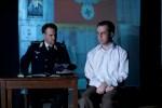 Rott (Steve Underwood) interrogates Bonhoeffer (Chase Byrd) against swastika background. Photo by © James Jackson.